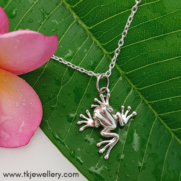 Sterling silver tree frog pendant displayed on leaf